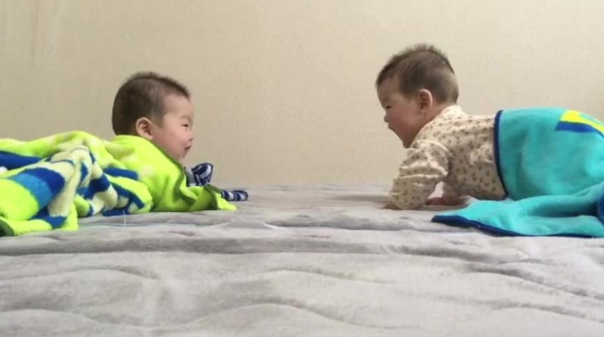 刚睡醒的双胞胎宝宝面对面趴着说话,笑嘻嘻的模样真可爱!
